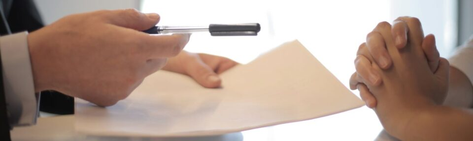 hands holding pen and paper