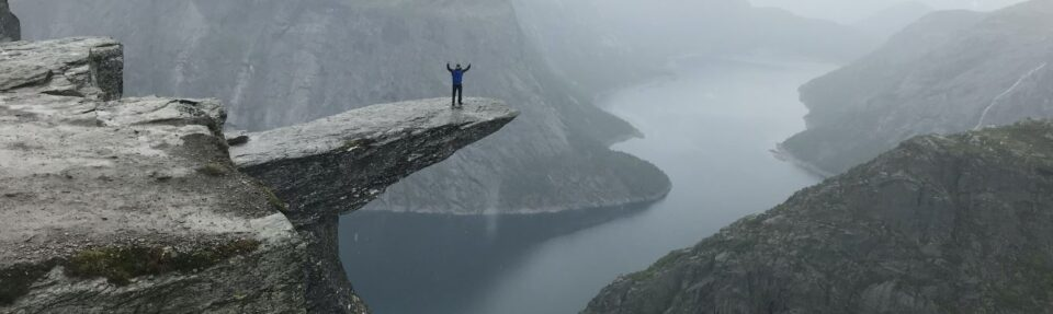 man on cliff overcoming challenges
