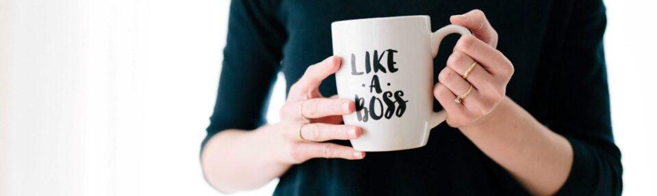 woman holding mug with like a boss writing